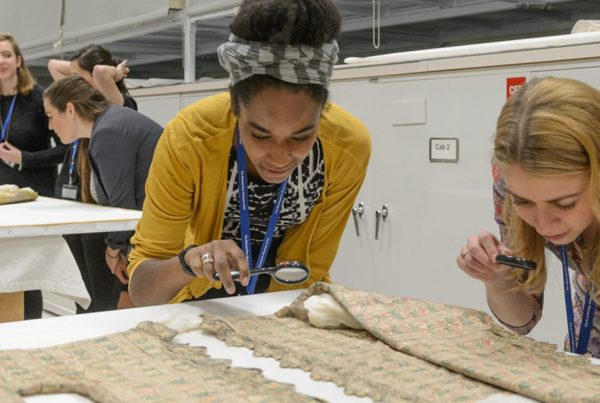 An intern reviewing a historical artifact alongside a museum-based researcher