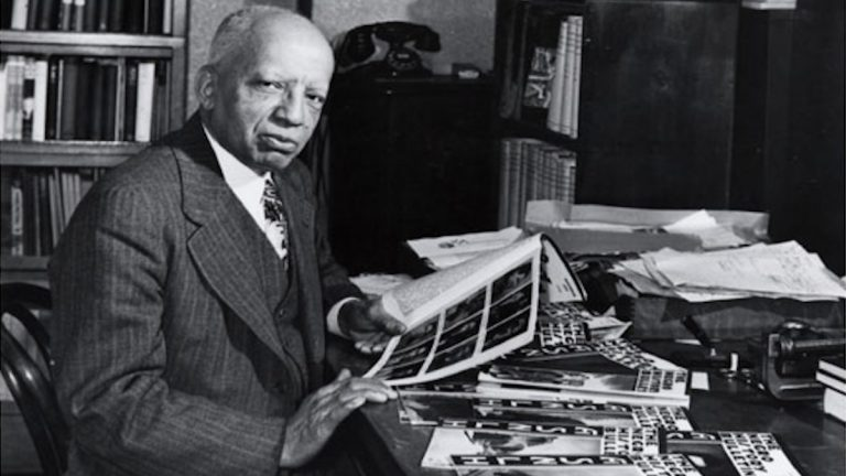 Dr. Carter G. Woodson looking at viewer while reviewing a book