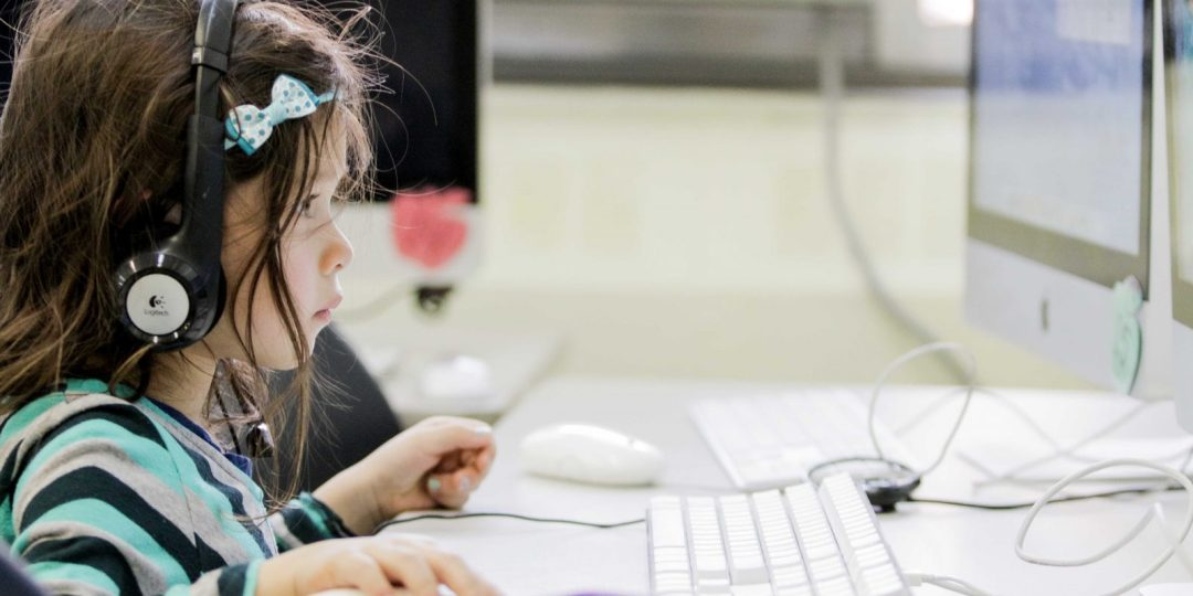Young student sitting at a computer with headphones on