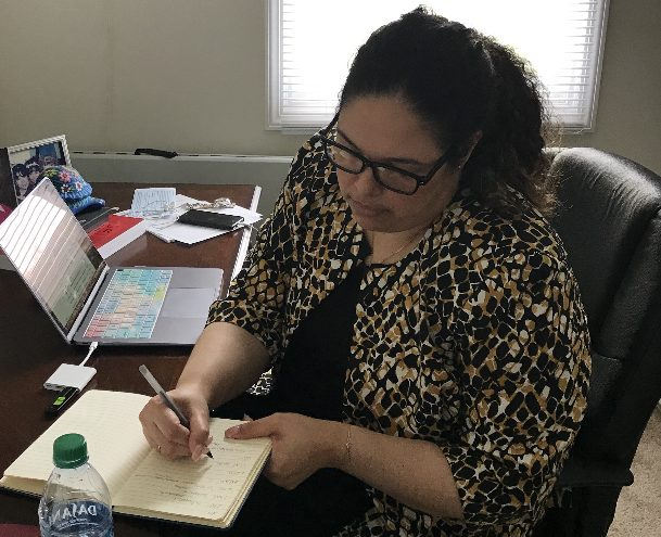 Principal Indira Mota writing on a notepad at her desk