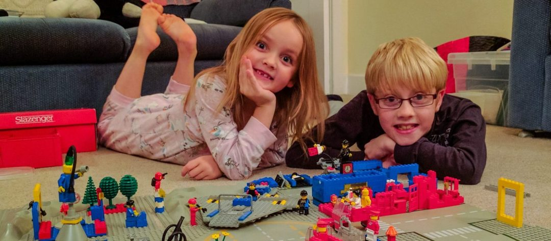 Two kids lying belly down next to a Lego playset they constructed