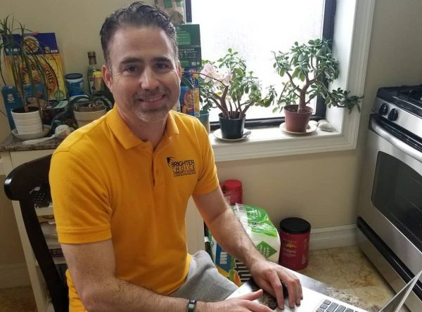 Principal Jeremy Daniel sitting in his kitchen while working on his laptop