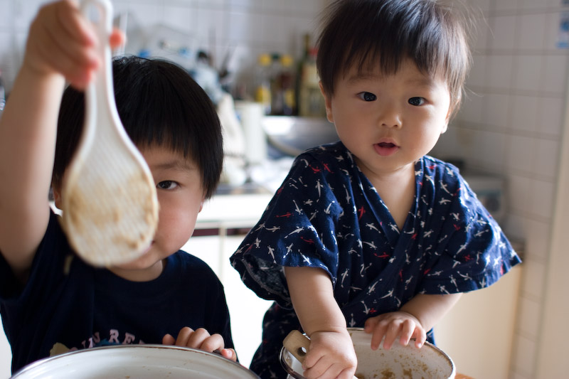 Two children using cooking utensils in a kitchen