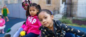 Three students sitting on a play tunnel in a school yard