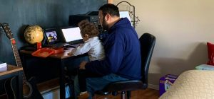 AP Dominic Armano sitting at his desk at home with his child