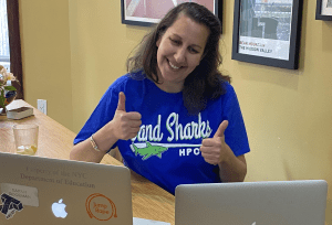Principal Sarah Goodman giving two thumbs up to two open laptops