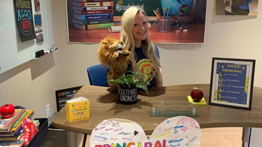 Justine Lucas with a lion at her desk