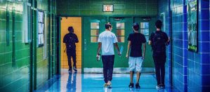 Backside of three high school students walking next to each other down a hallway