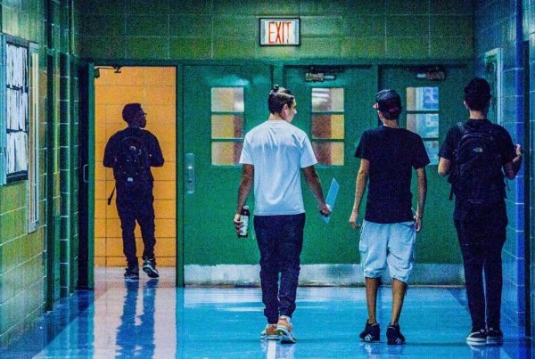 Backs of three high school students walking next to each other down a hallway