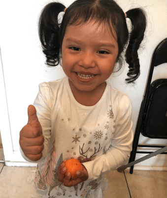 """Girl holding one thumb up to signify that the orange in her hand has a """"good smell"""""""