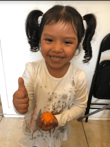 "Girl holding one thumb up to signify that the orange in her hand has a ""good smell"""
