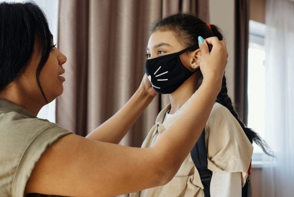 Mother placing a face mask on her daughter