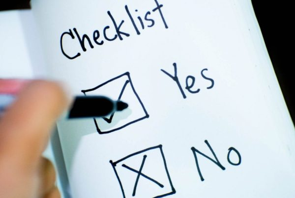 "Hand with marker hovering over a ""Yes"" checkbox on a sheet of paper entitled ""Checklist"""