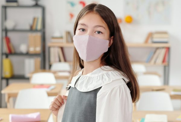 Girl with pink facemask standing in front of an empty classroom