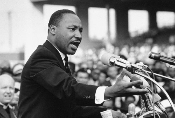Martin Luther King Jr. giving a speech at a podium with multiple microphones and surrounded by a sea of people