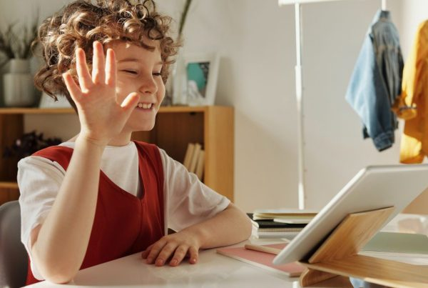 Middle school student waving at his tablet during a video call