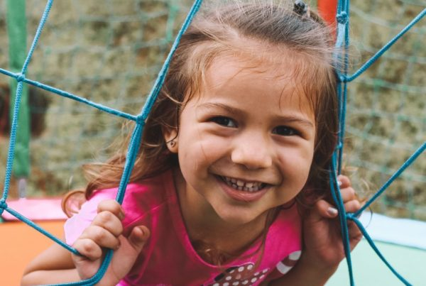 A child smiling while standing inside of a netted trampoline
