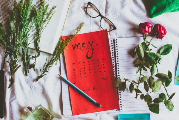 "A layout of ferns, a coffee mug, pen, glasses, an open notebook, and a calendar with ""May"" written on top"