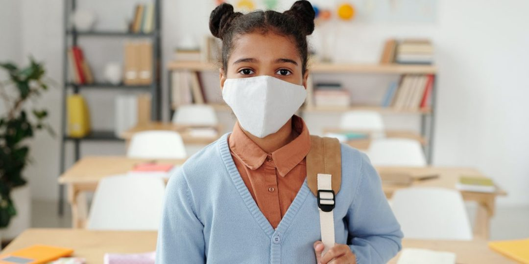 Student standing in classroom with facemask and bookbag on