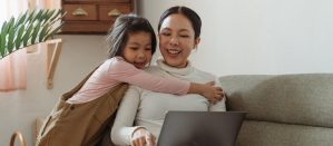 Woman sitting on a sofa with an open laptop and a girl hanging off her neck
