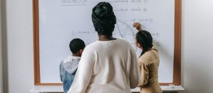 Back view of a teacher observing two students writing on a whiteboard in front of a classroom
