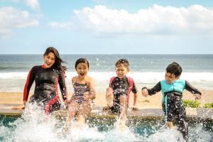 A woman sitting next to three children at the edge of a pool while splashing their feet.
