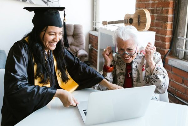 Graduate sitting next to grandmother while looking at a laptop together
