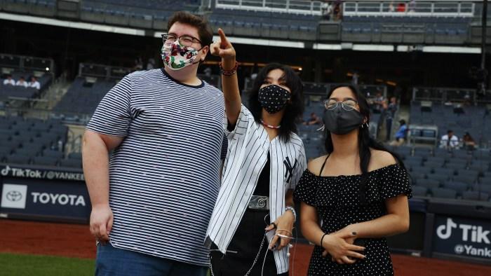 Three Yankees-Stonewall Scholarship Winners pointing to the stands at Yankee Stadium