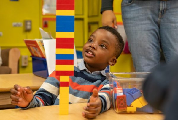 Early education student stacking a pile of Legos