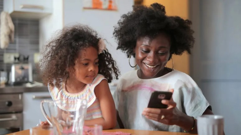 Girl looking at a smartphone being held by an adult while sitting in her lap inside of a kitchen