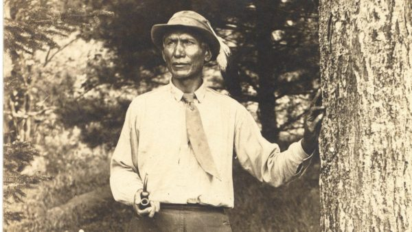 Charles Eastman with one hand on tree and other hand holding a smoking pipe