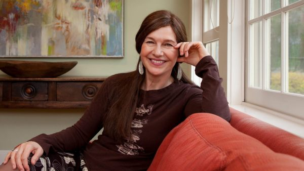 Pulitzer Prize winning author, Louise Erdrich, sitting on a red sofa