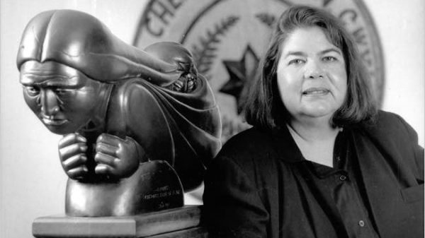 Wilma Mankiller (right) standing next to sculpture of Native American woman