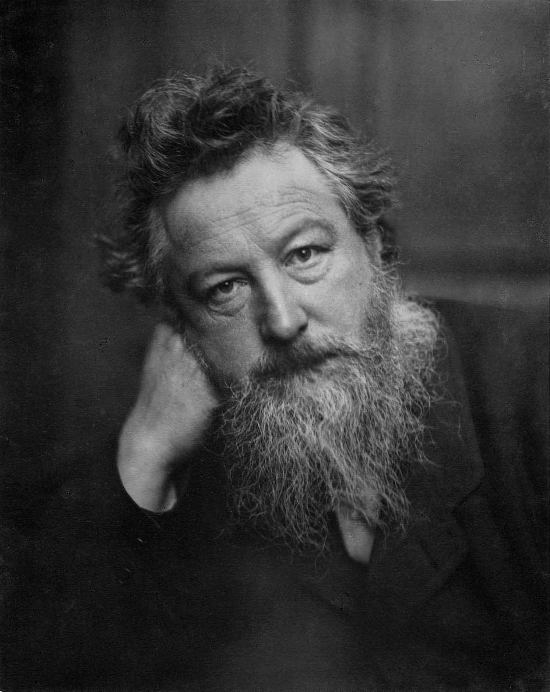 Black and white photograph of William Morris, an older man with a graying beard resting his head on his right fist.