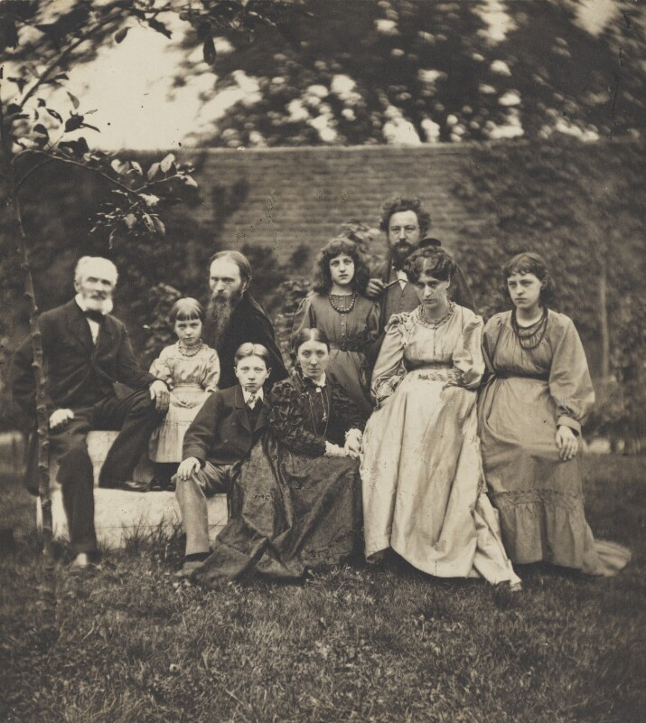 Group photograph of the Burne-Jones and Morris families, posed outside in a garden.