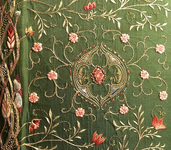 Embroidered book cover detail, threads in shades of gold and pink on green fabric. Design of stems and flowers.
