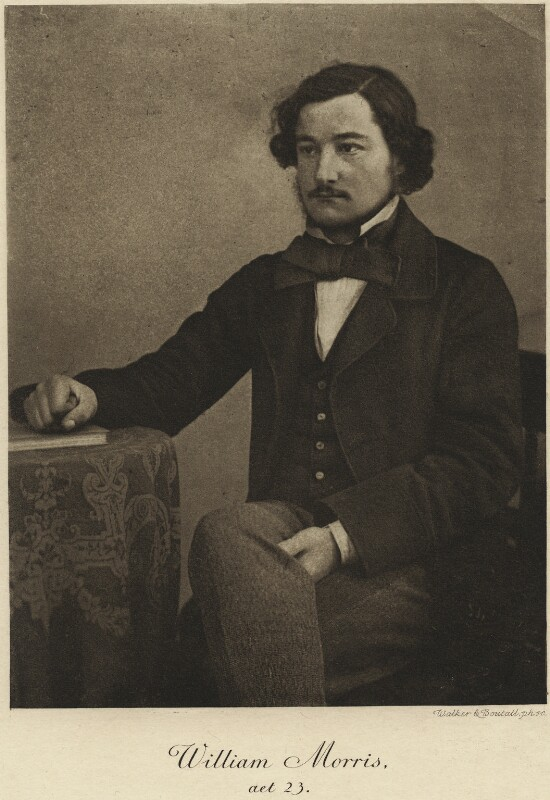 Photograph of William Morris, c. 1857. Sepia-toned image of a young man with dark hair and a neat beard, sitting posed with one hand on a table. He wears a dark suit and loose cravat tie, and lighter trousers.