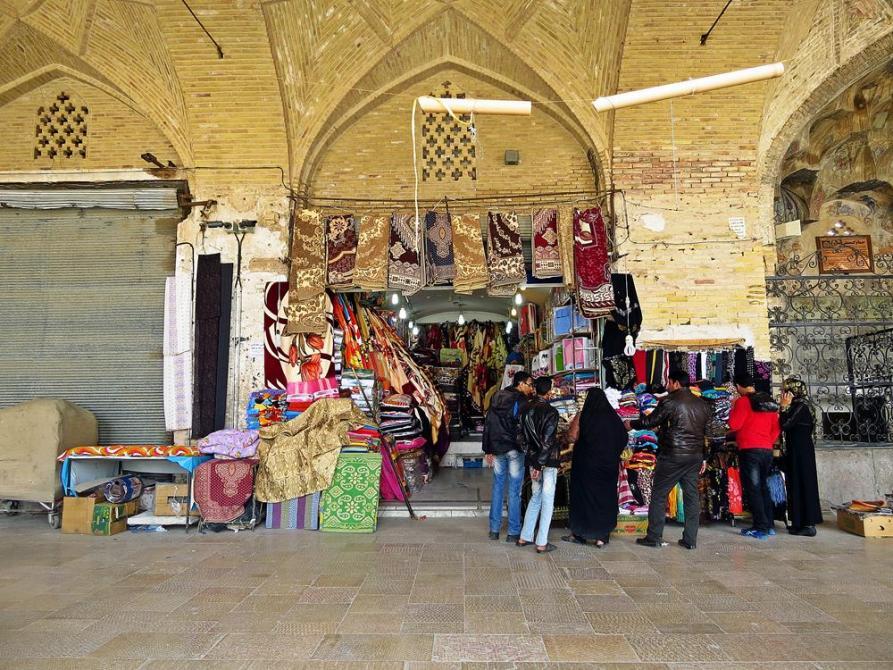 Stoff- und Teppichverkäufer auf dem Basar, Kerman