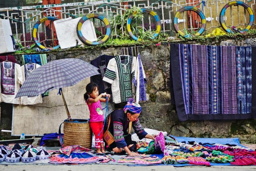 Schwarze Hmong verkauft traditionelle Stoffe in Sapa