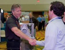 event photography of a handshake between a vendor and a convention attendee