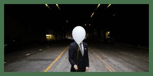 a men hiding his face with a balloom