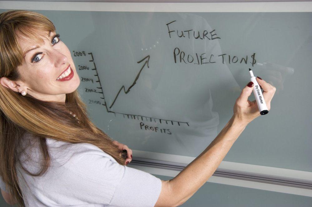 female teacher smilling writing on board