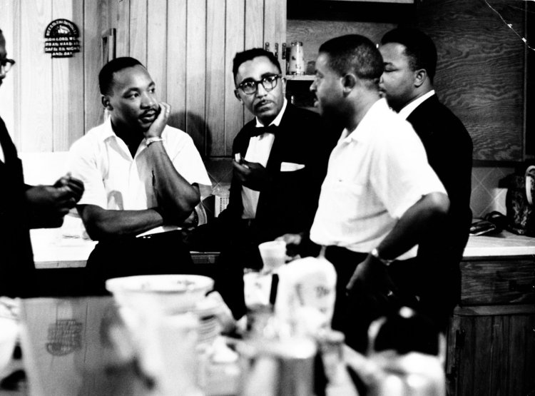Rev. Martin Luther King Jr. (C) speaking with Rev. Ralph Abernathy (2nd R) and others.