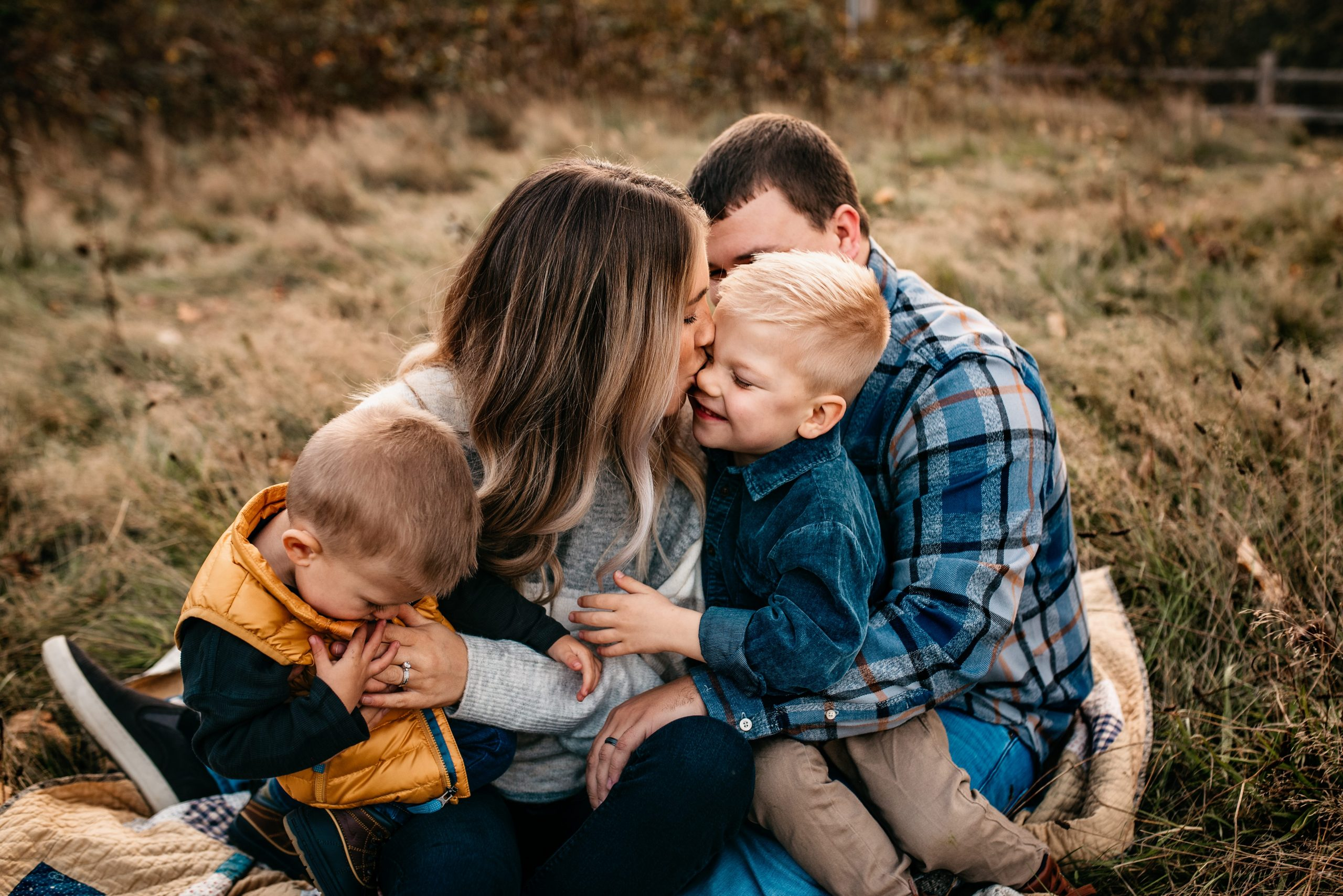 family of four sitting on a blanket during fall, mommy kissing son on the nose, all wearing fall clothes