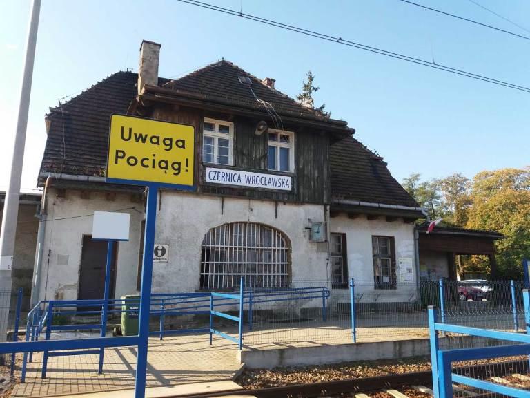 """Widok dworca od strony torów. Żółty znak ostrzegawczy """"Uwaga pociąg!""""."""