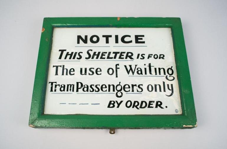 white sign with green border. tram shelter