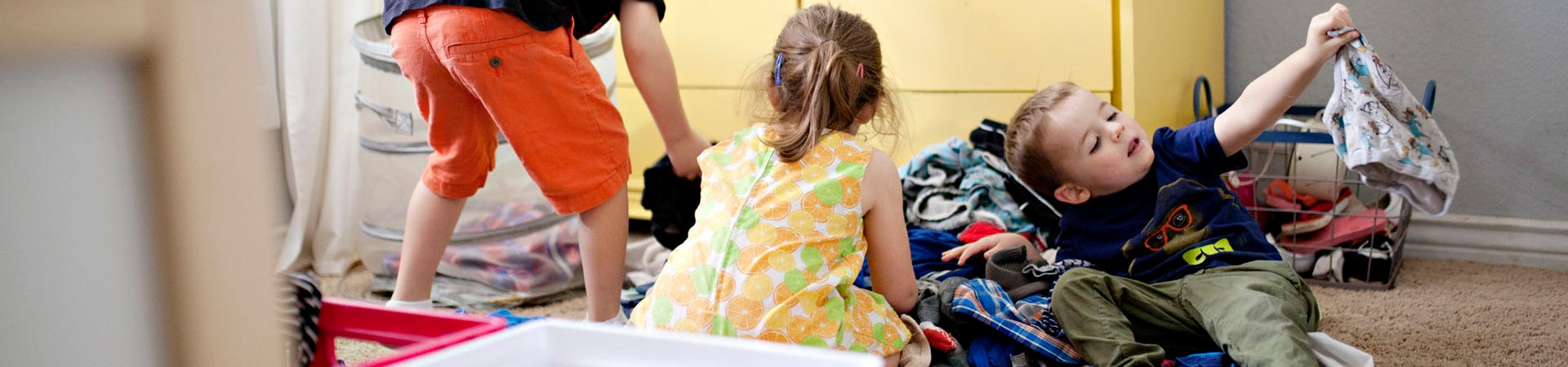 kids tidying their room sorting clothes