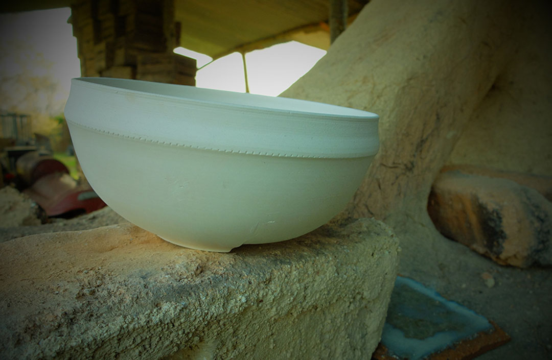 Photo d'une poterie brute posée sur un muret dans un hangar - référence