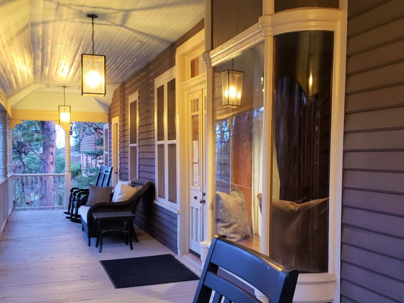 Spacious wrap-around porch with seating at the Outlook Lodge in Green Mountain Falls