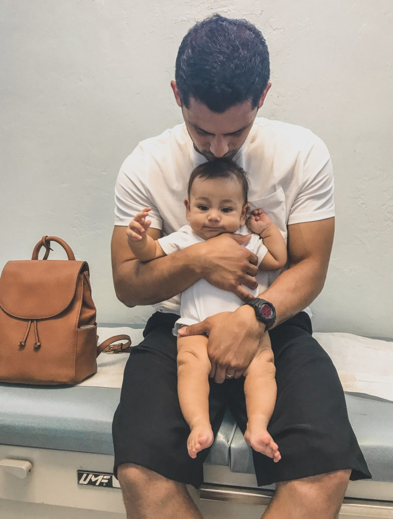 baby being held by father in doctors office getting first vaccines